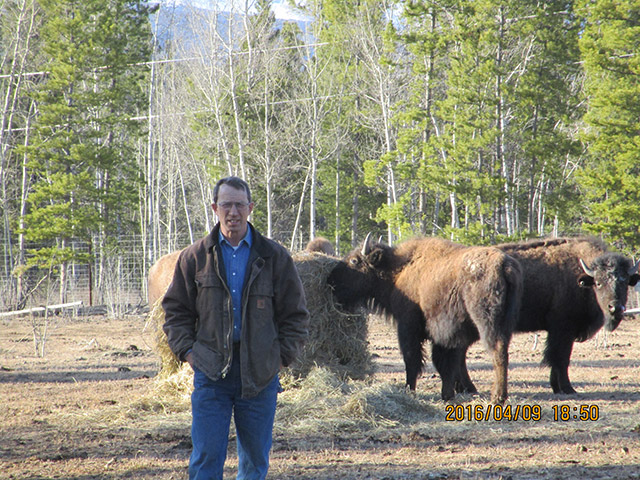 man with bison in the back